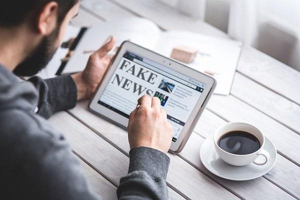 Homem lendo fake news em tablet